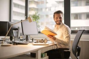 man sitting at desk with laptop smiling